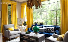 Vibrant yellow drapes surround this living room with a sunny embrace. Interior designer Amanda Nisbet heightened the drama by juxtaposing cobalt blue velvet next to the yellow drapes. Additional layering is created with pale shades of blue-grey in the upholstered chairs and a grey-blue geometric rug. A 1940's French chandelier with oak leaves in the color they turn in late fall brings more warmth. Image courtesy Amanda Nisbet's book Dazzling Design as featured in 1st dibbs.com