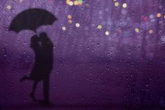 Blurred lover Kissing in the Rain with Umbrella and City light on the Street at night, See through Glass Window, Selective focus on droplet