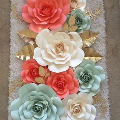 Gold, cora, ivoryl and mint large  paper flowers over  crib in  nursery.