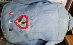 Tinkerbell Heart embroidery on the bottom back of a denim shirt.