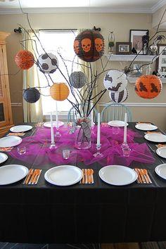 Decoracion de centro de mesa con ramas decoradas con lamparas de papel o globos chinos de halloween.
