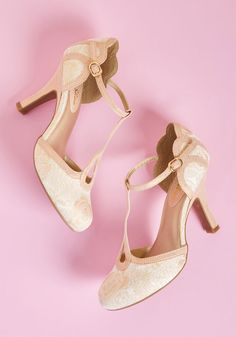 Ruby Shoo Dance Floor Dazzler T-Strap Heel in Blush - Spin, twirl, and shuffle your way across the room in these T-strap pumps from Ruby Shoo, and leave everyone in awe of your skill - and style! The drop-shaped cutouts, scalloped counters, and sleek pumps of this elegant pair are awash in a soft pink hue with metallic dots, coordinating gorgeously with the ivory brocade uppers and their touches of sparkling gold. With this pair, an encore is in order!