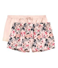 Short pajama shorts in satin with an elasticized waistband. One solid-color pair with lace trim at hems, and one patterned pair.