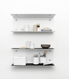 Vipp 921 vägghylla är tillverkad av en 3 mm aluminiumplåt som stansats ut och formats till en U-form som i sin tur skapar två hyllplan. Hyllan monteras med ett osynlig fäste 8 mm från väggen vilket ger ett flytande intryck. Hyllan fixeras med CNC-skurna skruvar i borstat rostfritt stål som skapar en subtil detalj i designen. Lika fin att använda i badrummet som i köket, vardagsrummet eller barnrummet.Finns i svart och vitt, och även i en längre variant - Vipp 922.