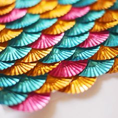 Take foil baking cups, fold them in half, glue them together in staggered rows, and you get… …fish scales! Or, since these are pink, aqua, and gold, mermaid scales! Isn't that the cutest (and easiest) idea for mermaid party backdrop? For an under the sea party, ...