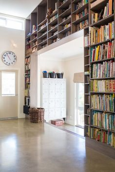 Floor-to-ceiling bookshelves and large clock.
