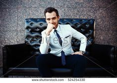 Young handsome bearded stylish man sitting on comfortable leather sofa outdoors #524254330