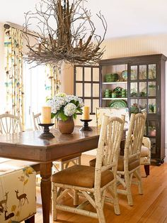 Simply Elegant:: Graced with rich natural textures and eclectic furniture -- such as birchwood-and-leather chairs -- this dining room's cozy appeal honors the home's mountainous location. A sculptural twig chandelier is a simple, unexpected touch that accentuates the dining area's warm, weathered feel. Printed fabric with graphic renderings of leaves and deer introduces fall flair with colors that unify the room's spectrum of earthy hues.