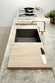 Benkeplaten på kjøkkenøya i Boforms nye Line One-kjøkken, er noe utenom det vanlige. Fior di Bosco-marmoren har en spennende fargepalett i grønt og grått og en marmorering som minner om patinert metall. Den 10 cm høye platen har et nedfrest platå, hvor en skjærefjøl og en hendig beholder til salt og pepper ligger stabilt og kan skyves frem og tilbake. Beholderen og fjølen er i eik, og armaturen i messing. Pris på forespørsel, boform.dk.