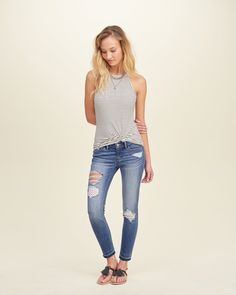 A cropped favorite pair in medium washed denim, detailed with a fading and whiskering effect, eyelet patching, heavy hand-done destruction, let-out hem and a five-pocket styling