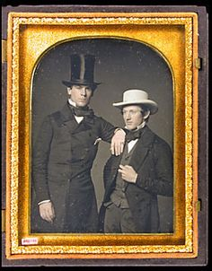 Two men wearing hats. Man on left wear silk top hat, frock coat. Man on right wearing sack coat, felt flat crown hat from The Daguerreian Society.