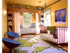 Here's a large, geography themed nursery, complete with world map rug and wall painting. Large crib stands under natural wood framing with bookshelves built into pillars, and globes on top. Twin blue chairs sit across from hammock-style couch.