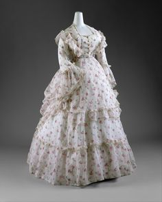 The 1870s was a period of marked romanticism and whimsy in fashionable dress.  Much like the picturesque paintings of Renoir that depict such confectionary creations, both day and evening gowns were highly ornamented and often executed in delicate, feminine textiles