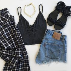 A lace-up top with a daisy choker, distressed shorts, strappy sandals, and a plaid shirt