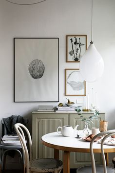 Dining room in retro chic with small round dining table, pastel green sideboard and awesome light in ballon shape