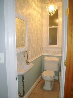 Tiny powder room idea: no wall paper, chair rail molding & chandelier!  bright colors, mirror