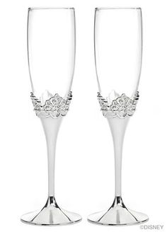 """Your happily ever after begins at your wedding reception with these sparkling Disney toasting flutes! The silver-plated stems gradually rise to the shape of a crown, accented with glittering rhinestones. Add two lines of your personalization to be engraved on each glass as a sweet memento of your wedding day.  Features and Facts:   Flutes are 9 1/4"""" tall.  Silver-plated metal base with glass bowl.  Note: This product is intended solely for non-commercial consumer use. No License has been…"""
