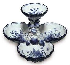AN ENGLISH DELFT BLUE AND WHITE SHELL-SHAPED SWEETMEAT DISH CIRCA 1755, PROBABLY LONDON Formed as a circular shell-molded bowl supported on a central column encrusted with small shells above three scallop-shaped bowls, the interior painted with insects among stylized flowers, raised on three conical feet