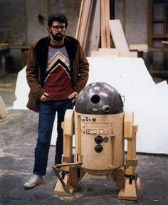 A very young George Lucas shown alongside an early wooden prototype of R2-D2.