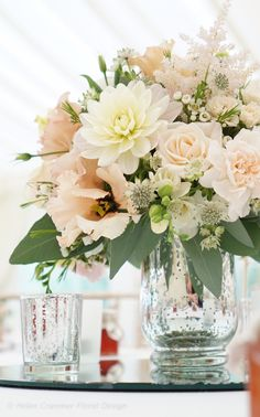 Peach & blush wedding centrepieces created by Helen Cranmer Floral Design. Flowers include roses, astilbe, wax flower, freesias, dahlia, eucalyptus, astrantia, lisianthus, veronica & gypsophilas.  Helen Cranmer Floral Design, London, Kent, Norfolk.