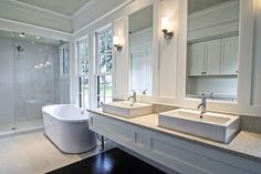 Lush white wood panel walls and vanity sandwich granite countertops and rectangular vessel sinks, hanging over a floor comprised of dark stained hardwood and beige tile in the bath area. Pedestal tub sits below large windows, next to glass panel shower.