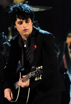Beautiful Billie Joe, handsome as hell with that gorgeous guitar, his fitted designer suit, and that gold chain with what looks like a Catholic saint medal. He is just perfect.
