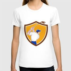 Golfer Swinging Club Crest Cartoon T-shirt. Illustration of a golfer playing golf swinging club tee off viewed from back rear set inside shield crest on isolated background done in cartoon style. #illustration #GolferSwinging