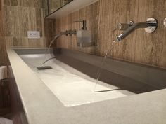 custom concrete sink by Trueform Concrete with wall mount faucets.