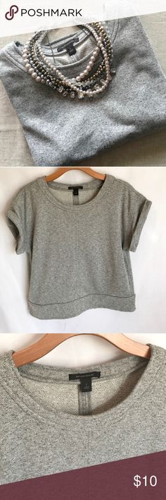 """{Banana Republic} Gray Cropped Short Sleeve Top Host Pick! This top is completely on trend! It is made of comfortable sweatshirt material but still looks dressy enough to wear for work or going out. Wear with a white long sleeve button down under it for a very classy look and a statement necklace. Hits right at the top of the hip. Top of shoulder to hem is about 22.5"""". Has a boxier fit for better layering. 70% polyester, 30% cotton. Banana Republic Tops"""