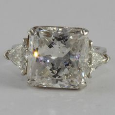 This graceful three-stone channel engagement ring shines with a Radiant Cut center stone diamond, all atop a band of small diamonds. Shown in Platinum with a 10.45 ct center stone. Total diamond weight is 11.46 carat.