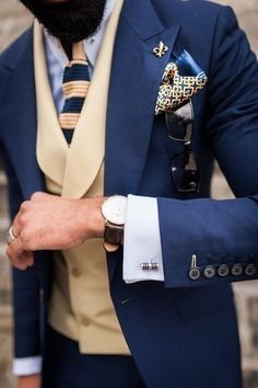 This suit is such an awesome piece. Blue and creamy colors run through everything from suit to vest to tie and pocket square and broach on the lapel. French cuff with cufflinks is a must for well dressed gentleman. Also a wristwatch. It is a finishing touch.