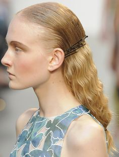Sleek hair pulled back, secured with hair pins combined with low wavy ponytail.