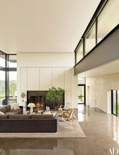 Interior designer collaborates with Lake|Flato Architects on her Texas ranch. In the living room, the steel fireplace surround is framed in eggshell-veneer panels by Chapeau Design.
