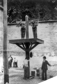 Two men in a pillory and one on a whipping post in a prison in Delware. 1907
