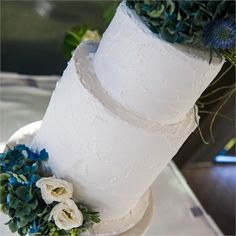 Ivory two-tiered wedding cake with blue flowers