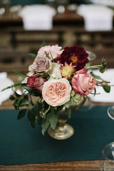 Centerpiece with soft blush, pink and deep red flowers.