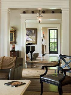 incredible cream trimwork, light taupe walls, black door, sisal, wood contrasts...love it all