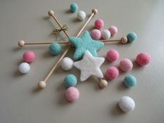 Quelques perles de laine feutrée et de jolies étoiles aux coloris tout doux... Un montage sur support mobile en bois naturel... La légèreté des perles de laine cardée feutrées à l'aiguille et le douceur des couleurs choisies pour cette composition sera...