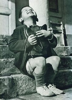 A joyful Austrian boy receives new shoes during WWII.