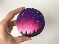 Take home this one of a kind galaxy wood round painting with a brightly colored, starry sky with tall trees. Let the beautiful rich pinks and purples inspire you and add excitement to your home!  This piece is one of a kind, and was handpainted with acrylic and ink. It is on a round wood slice that has been lightly painted with white to give it a bit of a rustic look to the edges. This piece would make an excellent gift for anyone, and would look great in an office, bedroom, living room…