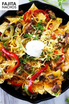 Steak Fajita Nachos is the best of the best when it comes to Mexican food appetizers! It's the perfect party food for Cinco de Mayo, but is hearty enough to stand along at the dinner table! Three crunchy layers of tortilla chips come fully loaded with tender bites of marinated flank steak, chopped peppers and onions, and melty Cheddar and Monterrey Jack cheese. Top it off with a dollop of sour cream and a heaping scoop of guacamole for a crowd-pleasing win at any party or any dinner table!