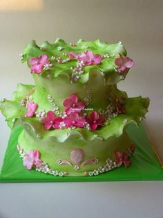 A very unusual small wedding cake, shades of green with pink flowers.  A green ruffle trims the cake and covers the anniversary tier.