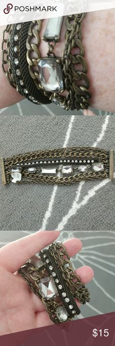 Jewel/chain layered bracelet Antique brass layered chain bracelet. Accented with varying sizes of rhinestones and types of chains. Magnetic closure. Never worn, still has tag attached. Perfect mix of edgy and feminine for that layered arm candy look! LOFT Jewelry Bracelets