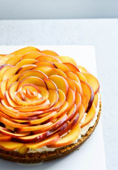 Whipped mascarpone peach tart - crumbly cookie crust filled with vanilla whipped mascarpone and topped with fresh peaches shaped like a rose! A truly impressive dessert. | mitzyathome.com