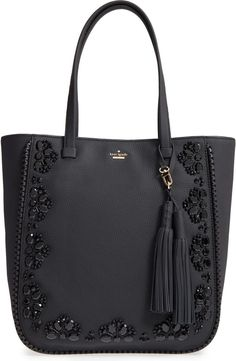 Hand-stitched jet-black beads add just the right amount of glint to this gorgeous pebbled-leather bag, while laser-cut whipstitched trim beautifully frames the embellished exterior. An optional tassel charm adds a swingy touch to the elegant style.