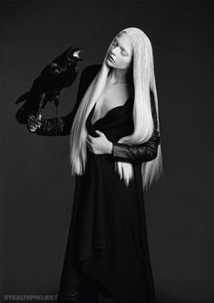 White/blonde long haired woman holding a raven