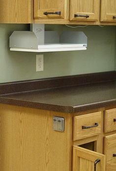 An unobtrusive electrical switch can lower cabinet contents within easy reach of those confined to a wheelchair