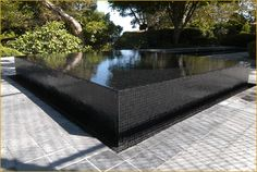 a bit too 70s modern for my tastes, but nice reflecting pool effect. black glass tile spa by Skip Phillips