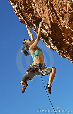 Female rock climber struggles up a cliff for her next grip on a challenging ascent.