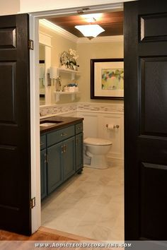 DIY bathroom remodel with tile floor, stained wood slat ceiling, DIY vanity, recessed panel walls, and bifold closet doors used as double doors